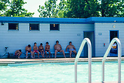 Young boys sitting on a bench next to the mens' dressing room at the public swimming pool in Beardstown, Illinois