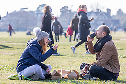 © Licensed to London News Pictures. 07/03/2021. London, UK. Husband and wife, Andrew 33 and Nicci Kinsler 29 from Wimbledon enjoy a picnic together on Wimbledon Common in the sunshine this afternoon. From Monday, 8th March 2021 two friends will be allowed to socialise out side of their household for a coffee or picnic for the first time in months. England will begin Stage1 of the easing of lockdown tomorrow, with children returning to school, care homes allowing a visitor and friends being allowed to socialise out side of their household. However, pubs, shops and restaurants will still remain closed. Photo credit: Alex Lentati/LNP
