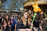 Group of young people, probably tourists, and one holding a large smiling flower, out for the day along the South Bank in London, England, United Kingdom. The South Bank is a significant arts and entertainment district, and home to an endless list of activities for Londoners, visitors and tourists alike.