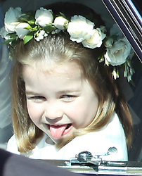 A flower girl sticks out her tongue as she rides in a car to the wedding at St George's Chapel in Windsor Castle of Prince Harry and Meghan Markle.