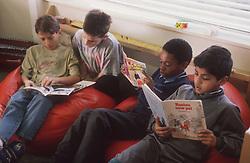 Junior school pupils reading story books in book corner,