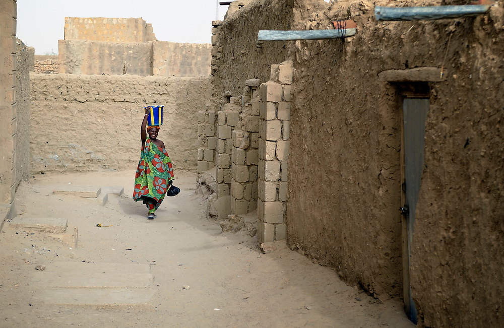 Carrying water on her head, a woman walks along a street in Timbuktu, the northern Mali city that was seized by Islamist fighters in 2012 and then liberated by French and Malian soldiers in early 2013. During jihadist rule, women and girls were not permitted in public unless they were completely covered.