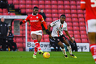 Mamadou Thiam of Barnsley (26) passes the ball under pressure from Anfernee Dijksteel of Charlton Athletic (2) during the EFL Sky Bet League 1 match between Barnsley and Charlton Athletic at Oakwell, Barnsley, England on 29 December 2018.