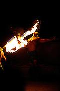 Male Hawaiian fire dancer, licking flame. Hawaii