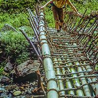 A trekker crosses a bamboo bridge over a stream in the Marsyandi River Valley, Nepal.