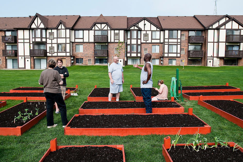 Matt Dixon | The Flint Journal..Residents at Charter Oaks Apartments in Davison, from left, Diane MacDonald, 61, Thomas Moore, 28, Tom Cartel, 52, Julius Olayinka, 46, and Tessa Ruff, 18, discuss gardening while preparing to plant Thursday morning. The apartment complex recently installed these 4-feet-by-10-feet garden plots which residents can rent to grow their own fruits, vegetables, and plants.