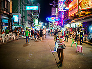 24 JULY 2018 - BANGKOK, THAILAND: A woman trying to sell hammocks to tourists on Khao San Road in Bangkok. Khao San Road is Bangkok's original backpacker district and is still a popular hub for travelers, with an active night market and many street food stalls. The Bangkok municipal government plans to shut down the street market by early August because city officials say the venders, who set up on sidewalks and public streets, pose a threat to public safety and could impede emergency vehicles. It's the latest in a series of night markets and street markets the city has closed.   PHOTO BY JACK KURTZ