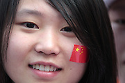 A young Chinese woman wears a Chinese flag sticker on her cheek at the Olympic Torch relay in the southern city of Wuhan