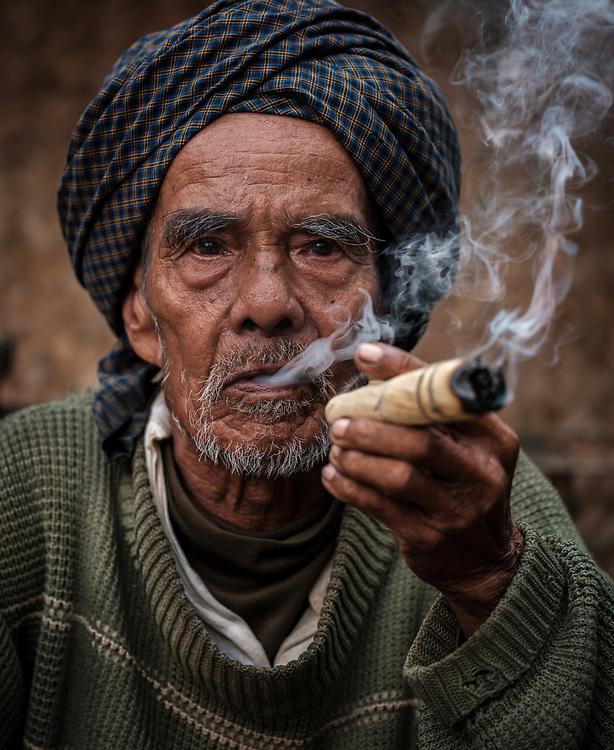BAGAN, MYANMAR - CIRCA DECEMBER 2017: Old man from a village around Bagan moking.
