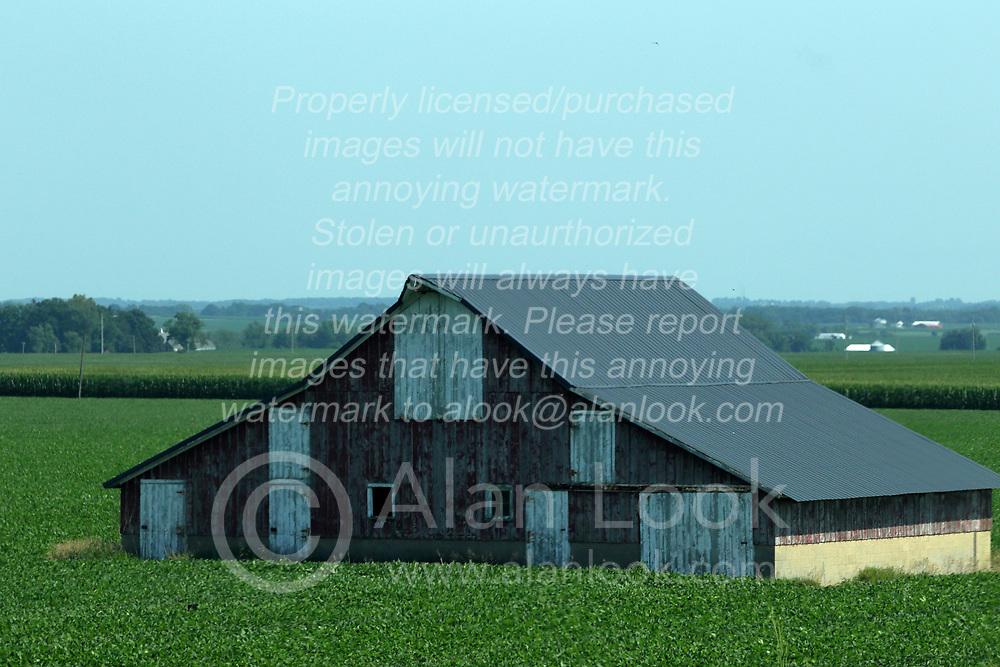 Wooden frame construction barn in field