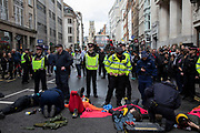 Climate change activists from the Extinction Rebellion group are cut free after being locked on and glued together outside Goldman Sachs International on Fleet Street in the heart of the City of London financial district in protest that the government is not doing enough to avoid catastrophic climate change and to demand the government take radical action to save the planet, on 25th April 2019 in London, England, United Kingdom. Extinction Rebellion is a climate change group started in 2018 and has gained a huge following of people committed to peaceful protests.