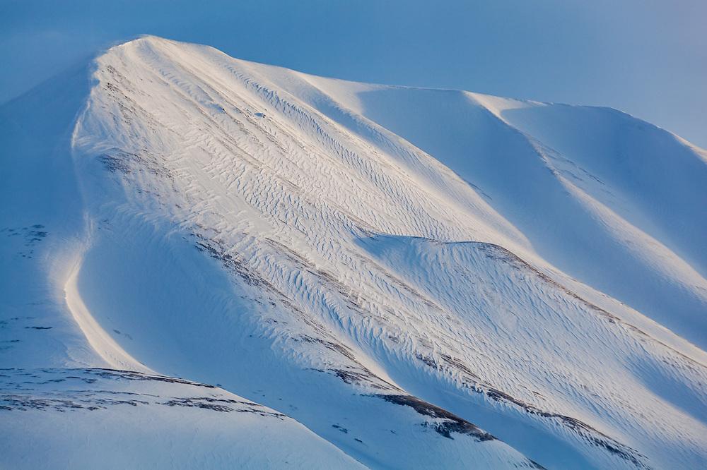 Windswept slopes of Hallwylfjellet, Svalbard at sunrise.