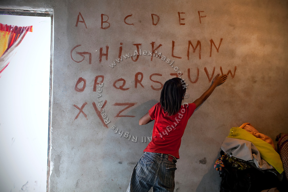 Poonam's older sister Jyoti, 10, is learning the English alphabet written in large letters on a wall inside her family's newly built home in Oriya Basti, one of the water-contaminated colonies in Bhopal, central India, near the abandoned Union Carbide (now DOW Chemical) industrial complex, site of the infamous '1984 Gas Disaster'.