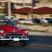 Central America, Cuba, Havana. Classic convertible car driving along the Malecon in Havana.