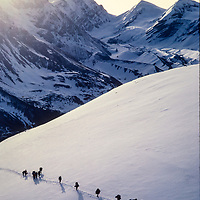 A line of porters carry loads for trekkers crossing 17,769' Thorang La pass during a trek around Annapurna in Nepal.