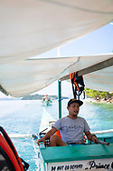 Prince, from Port Barton, steers a boat carrying several tourists past Turtle Spot, a popular snorkeling spot where, as the name suggests, one has a good chance of seeing sea turtles.<br /><br />(July 7, 2019)