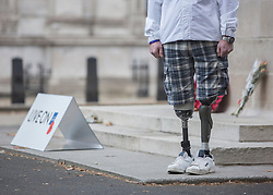 © Licensed to London News Pictures. 23/10/2014.  London.  The Royal British Legion launched the 2014 Poppy Appeal at sunrise this morning at the Cenotaph memorial.  Former Royal Marine Commando Peter Dunning (28) from Wallasey who lost both his legs in an IED blast in Afghanistan in 2008 and now a member British Army's Ski Team  took part in a 30 minute vigil to commemorate fallen soldiers of WW1.  The Poppy Appeal is The Royal British Legion's largest annual charity campaign. In a little over two weeks, some 45 million poppies will be distributed by 350,000 dedicated collectors with the aim of raising £40 million.        Photo credit : Alison Baskerville/LNP
