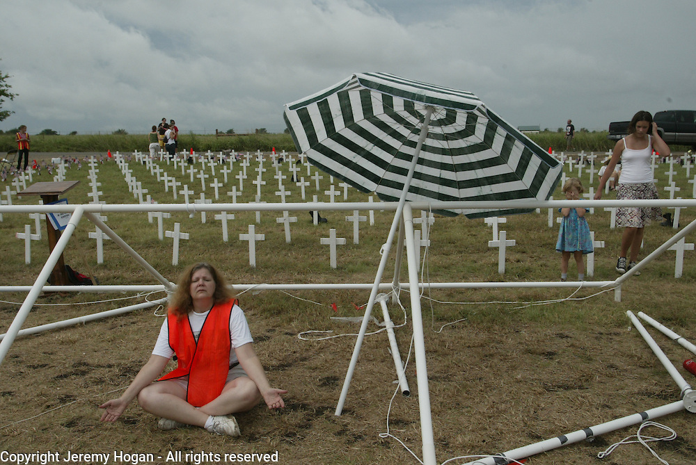 an anti-war activist meditates near crosses at Camp Casey II which represent U.S. soldiers killed in Iraq