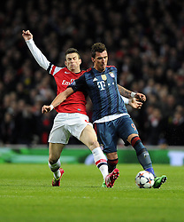 Arsenal's Laurent Koscielny tackles Bayern Munich's Mario Mandzukic  - Photo mandatory by-line: Joe Meredith/JMP - Tel: Mobile: 07966 386802 19/02/2014 - SPORT - FOOTBALL - London - Emirates Stadium - Arsenal v Bayern Munich - Champions League - Last 16 - First Leg