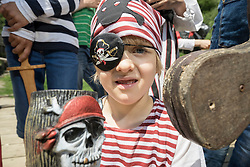 Portrait of a boy dressed up as a pirate on a pirate ship with his friends standing behind him, Bavaria, Germany