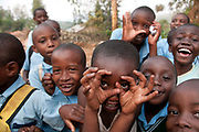Rwanda February 2014. Kigali. Children coming home from school, laughing with one making 'camera eyes' at the photographer