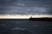 A stormy day with dark clouds looms over the lighthouse on Folkestone Harbour Arm, with France in the distance, 6th October 2016, Folkestone, Kent, United Kingdom.