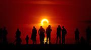 Viewers at Dog Beach in San Diego, California, USA, watch an annular solar eclipse in progress.