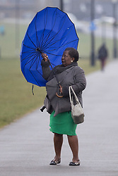 © Licensed to London News Pictures. 10/03/2021. London, UK.  A woman struggles with an umbrella as she walks on a wet and windy Blackheath Common in South East London . A yellow weather warning for wind is in place in parts of the UK. Photo credit: George Cracknell Wright/LNP