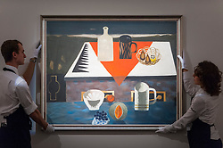 """© Licensed to London News Pictures. 18/11/2016. London, UK. Technicians prepare to hang """"The Red Cloth"""" by Mary Fedden (est. GBP15-20k), at the preview at Sotheby's of works on view at four upcoming November auctions featuring Modern & Post-War British Art, A Painter's Paradise (Julian Trevelyan & Mary Fedden at Durham Wharf), Scottish Art and Picasso Ceramics from the Lord & Lady Attenborough Private Collection. Photo credit : Stephen Chung/LNP"""