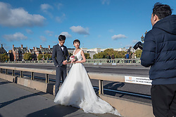 © Licensed to London News Pictures. 05/11/2017. London, UK.  A mainland Chinese couple pose for pre-wedding photographs being taken on Westminster Bridge.  With Sterling's decline, London is seen as an ever more affordable location for such photographs, as well as providing memorable landmarks as backdrops.  Frequently, the photographer and team are also flown out from China to capture the images.  Photo credit: Stephen Chung/LNP
