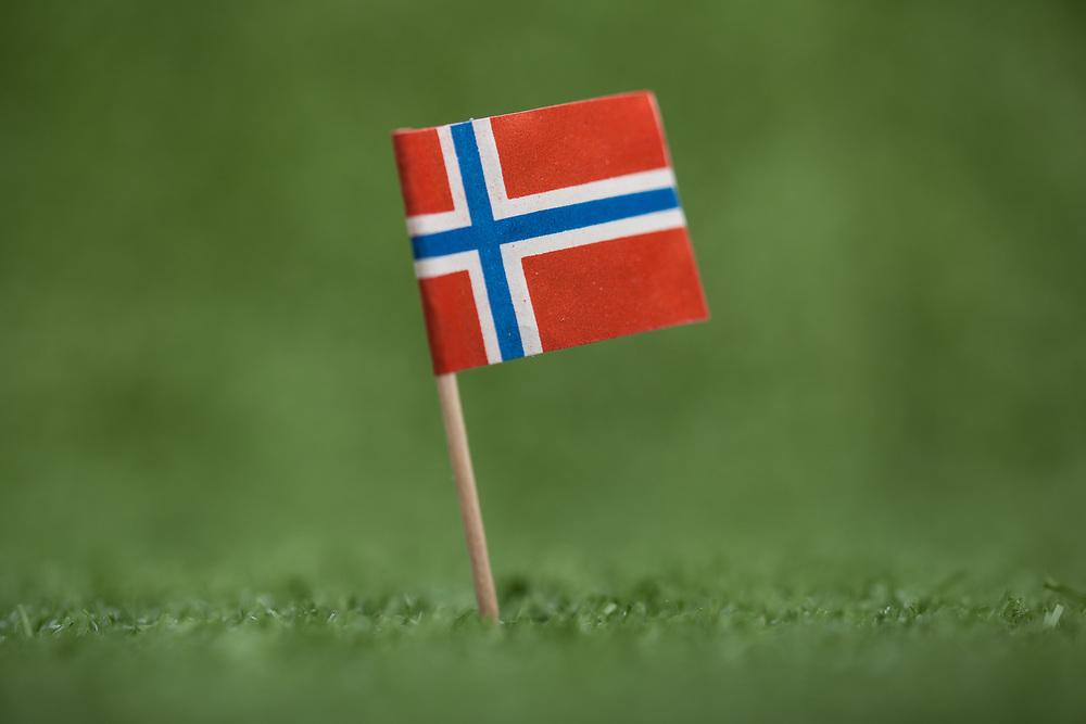 Enslig, norsk flagg med trepinne på grønt kunstress. Foto tatt med macro-objektiv, stor dybdeuskarphet. God plass til tekst, spesielt egnet som bakgrunnsbilde.