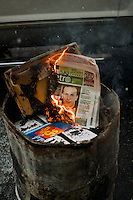 A metro paper is used to start a 55 gallon barrel fire on Washington Ave. in front of Giordano's Market in Philadelphia's Italian Market.
