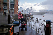 """A woman and child brave a rainshower at Butler's Wharf while the superyacht 'Kismet' is moored downstream on the river Thames from Tower Bridge and the capital's financial district's skyscrapers, on 20th October 2021, in London, England. 'Kismet' is a 95.2m (312 ft)-long superyacht which was built in 2014. It is managed by the Moran Yacht & Ship chartering business, and is owned by Pakistani-American billionaire Shahid Khan. 'Kismet' means """"destiny"""" or """"fate"""" in Khan's native Urdu."""