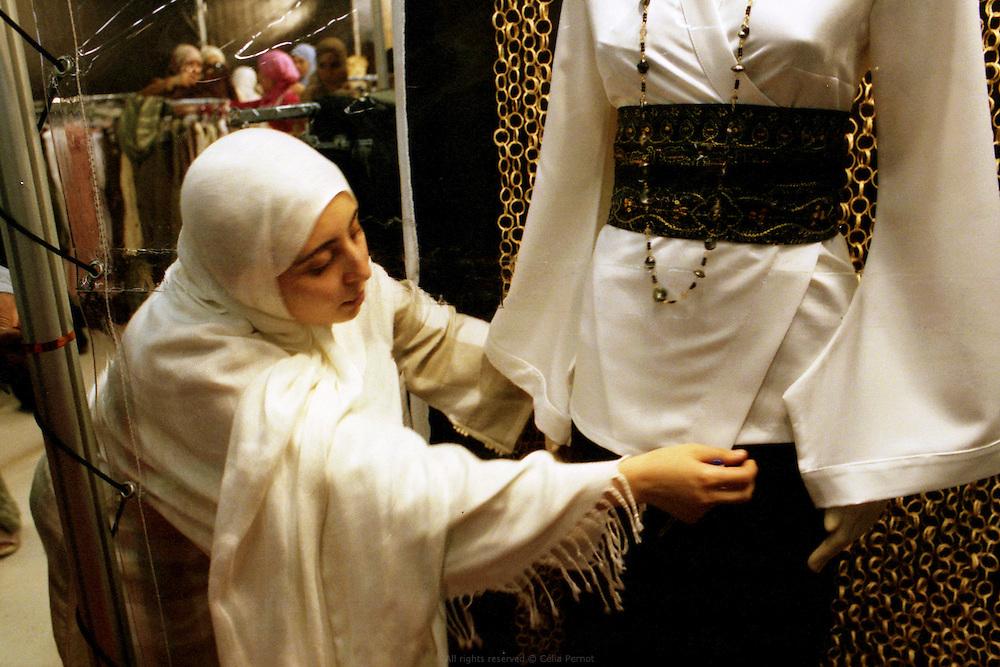Karima Saouli préparant la vitrine de son stand à la rencontre annuelle des Musulmans de France au salon du Bourget, 2006. <br /> Karima Saouli, pioneer of muslim fashion design, arranging her booth at the French Muslims' annual meeting, Bourget fair, 2006.