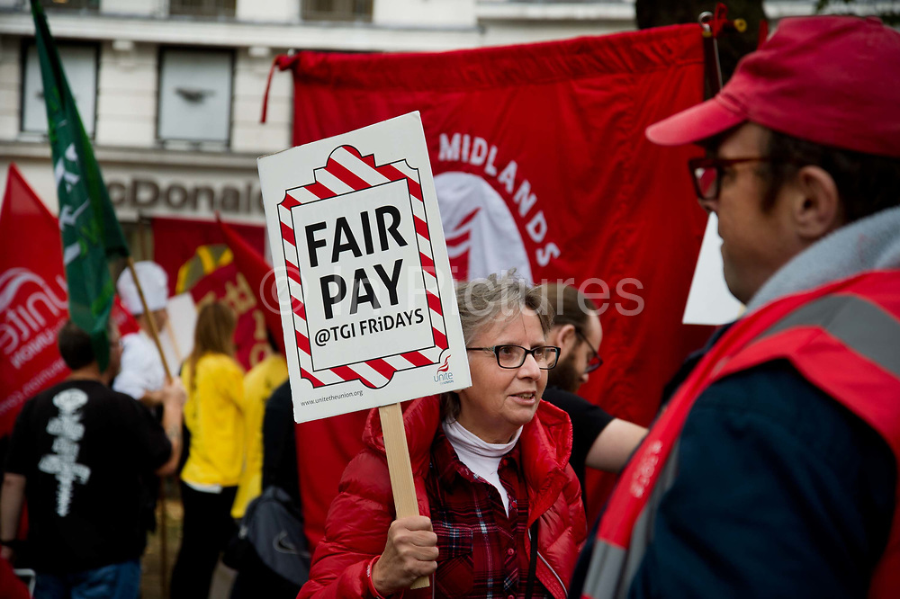 Food service industry workers strike for higher wages on October 4th 2018 in Leicester Square, London, United Kingdom. Day of action by workers from TGI Fridays, McDonalds; Deliveroo and Wetherspoons, supported by TUC and Labour Party, demanding better conditions for the hospitality sector. A woman holds a placard saying Fair Pay.