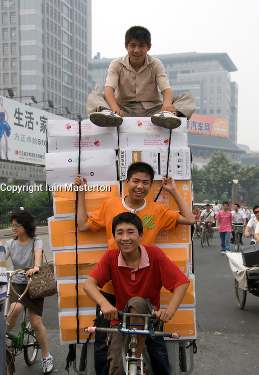 Young men on tricycle making delivery of computers in Zhongguacun high technology district of Beijing China