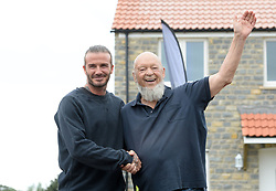David Beckham (left) and Michael Eavis pose for photographs outside a completed house in a housing development in Pilton village in Somerset.