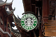 Starbucks coffee shop by Chinese streetsigns in the Yu Garden Bazaar Market, Shanghai, China
