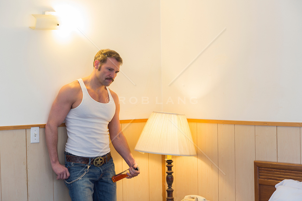 redneck man in a sleeveless tee shirt holding a bottle of Jack Daniels in a cheap motel room