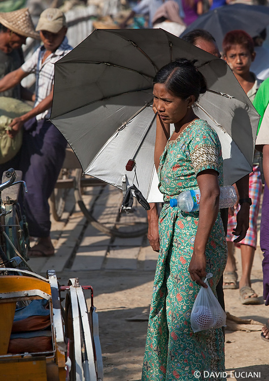 A woman carrying an umbrella to block the midday sun on a noisy street in Mrauk U.