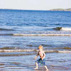A boy (age 6) skim boarding at Popham Beach State Park in Phippsburg, Maine.