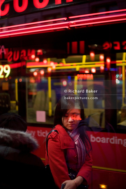 Commuters on red bus route at stop in Charing Cross Road in central London.