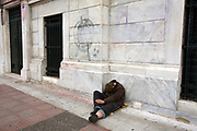 A homeless man asleep whilst begging near Syntagma Square, Athens, Greece