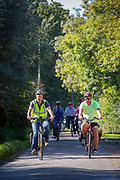 A group of cyclists ride along a country road in Staplehurst, Kent, England, UK.  They are riding electric bikes.
