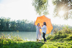 Couple having fun under the sunshade at riverbank, Bavaria, Germany