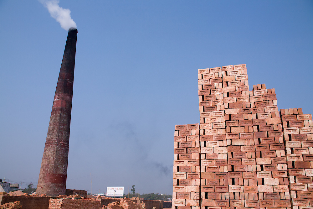 A pile of bricks with a smoketack in the background, Bangladesh.
