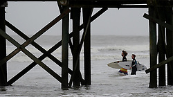 Surfers pass a pier on Oct. 7, 2016 at the Isle of Palms, S.C. Hurricane Matthew is scheduled to skirt the coast of South Carolina later Friday or early Saturday morning. Photo by Jeff Siner/Charlotte Observer/TNS/ABACAPRESS.COM