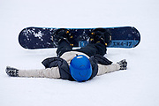 Female snowboarder collapsed after a run.