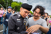 """24 JUNE 2014 - BANGKOK, THAILAND: A Thai police officer (left) talks to a poet (right) after he read it aloud at a meeting of the Monsoon Poets Society in Bangkok. Members of the """"Monsoon Poets Society"""" gathered in front of the Anantasamakom Throne Hall Tuesday to pay homage to the People's Party, a Siamese (Thai) group of military and civil officers (which became a political party) that staged a bloodless coup against King Prajadhipok (Rama VII) and changed Thailand (then Siam) from an absolute monarchy to a constitutional monarchy on 24 June 1932. Since the coup against the civilian government on 22 May, the ruling junta has not allowed political gatherings. Although police read the poems, they did not arrest any of the poets or make any effort to break up the gathering.     PHOTO BY JACK KURTZ"""