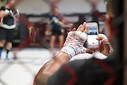 UFC featherweight Anthony Pettis of Wisconsin takes a Snapchat while his brother UFC flyweight Sergio Pettis hits mitts at Jackson Wink MMA in Albuquerque, New Mexico on June 9, 2016.